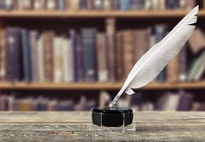 Feather quill pen and glass inkwell on library Stock Images