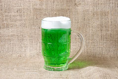 Glass of Irish green beer on a burlap background Stock Photos