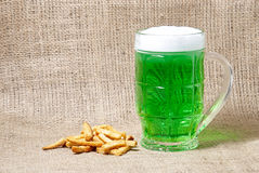 Glass of Irish green beer and crackers on a burlap background Royalty Free Stock Photo