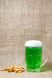 Glass of Irish green beer and crackers on a burlap background Royalty Free Stock Images