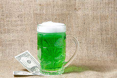 Glass of Irish green beer and dollars on a burlap background Stock Photos