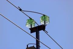Glass isolatorer av en överföringslinje stöttar närbild på bakgrund för blå himmel royaltyfri fotografi