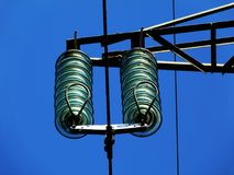 Glass Electrical Isolators and Powerlines. Glass isolators on high voltage electrical line and steel power structure and blue sky Royalty Free Stock Photography