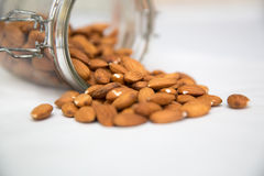 Glass Jar of Almonds. A jar of almonds being spilt Royalty Free Stock Photography