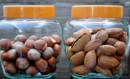 Glass jar with almonds and hazelnuts Royalty Free Stock Photos