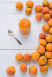 Glass jar of apricot puree of fresh apricots. Glass jar of apricot puree of fresh apricot,teaspoon and apricots on white wooden table royalty free stock photography