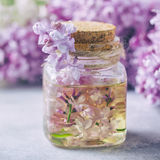 Glass jar with aroma oil and with lilac flowers for spa and aromatherapy. Spa concept. Selective focus Royalty Free Stock Images
