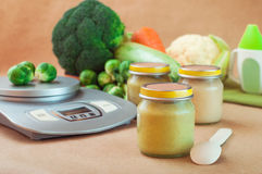 Glass jar with baby food near kitchen scales Royalty Free Stock Photography