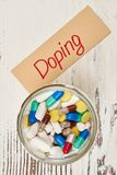 Glass jar of banned drugs. And Doping lettering. Tablets and capsules. Crime in sports Royalty Free Stock Photos
