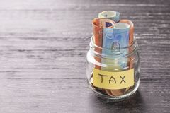 Glass jar on a black wooden table with coins and euro banknotes and the words TAX royalty free stock photo