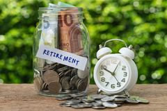 Glass jar bottle labeled as retirement with full of coins and ba. Nknotes, white alarm clock as savings or investing for retirement concept Stock Photos
