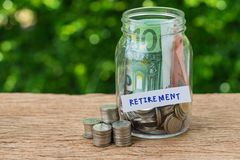 Glass jar bottle labeled as retirement with full of coins and ba. Nknotes as savings or investing for retirement concept Royalty Free Stock Image