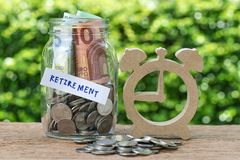 Glass jar bottle labeled as retirement with full of coins and ba. Nknotes, wooden alarm clock as savings or investing for retirement concept Stock Photography