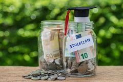 Glass jar bottles with full of coins labeled as Education and gr Royalty Free Stock Photo