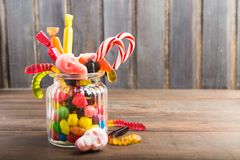 Glass jar with candies for halloween on wooden background. Copy space Stock Photos