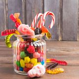 Glass jar with candies for halloween on wooden background. Square shot Stock Image