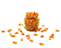 Glass Jar of Candy Corn. Small glass container filled with candy corn with pieces scattered on white background Royalty Free Stock Image