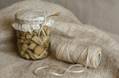 Glass jar with canned wild mushrooms on burlap