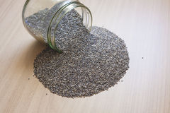 Glass jar with chia seeds spilt over wooden surface Stock Images