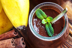 Glass jar with chocolate pudding or mousse with fresh banana, mint and cinnamon sticks over a wooden table. Sweet dessert Royalty Free Stock Image