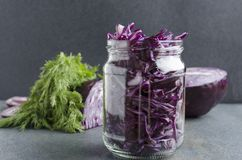 Glass jar with chopped fresh red cabbage,dill and rings of onion- preparation for fermentation on the grey surface in the kitchen. stock images
