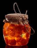 Glass jar with citrus zest preserves isolated on black Stock Photos