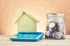 Glass jar with coins, calculator and home replica on wooden desk. For home loans concept stock photo