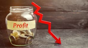 Glass jar with coins, down arrow and word Profit. Unsuccessful business and poverty. Profit decline. Loss of investment. Low wages. Economic crisis. The fall stock photography