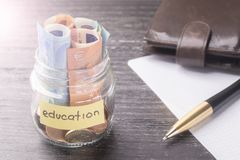 Glass jar with coins and euro banknotes with the words EDUCATION. Pen, blank sheet of paper and leather wallet stock photos