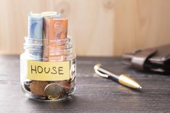 A glass jar with coins and euro bills with the word HOUSE on a black wooden table. Pen and leather wallet stock photos