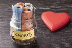 Glass jar with coins and euro notes with the inscription CHARITY. With a huge red heart royalty free stock photography