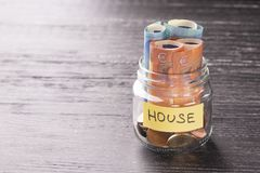 Glass jar with coins and euro notes with the word HOUSE on a black wooden table stock images