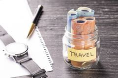 Glass jar with coins and euro notes with the word TRAVEL on a black wooden table. Wrist watch, pen and blank paper stock photography