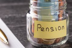 Glass jar with coins and euro notes with the words PENSION. Pen and blank note paper royalty free stock images