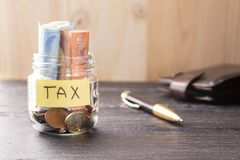 Glass jar with coins and euros with the inscription TAX on a black wooden table. Pen and leather wallet stock images