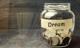 Glass jar with coins and the inscription `Dream`. Family budget and finances. Distribution of cash savings. Fulfilling a cherished stock image