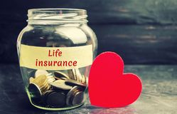 Glass jar with coins and the inscription `Life Insurance`. The concept of medical insurance of life, family, health. Healthcare. R. Ed heart. The accumulation of royalty free stock photos