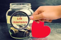 Glass jar with coins and the inscription `Life Insurance`. The concept of medical insurance of life, family, health. Healthcare. R. Ed heart. The accumulation of stock photos