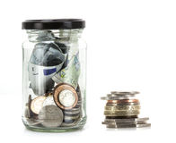 Glass jar with coins and notes Royalty Free Stock Image