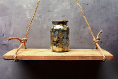 Glass jar with coins on the old wood shelf Stock Image