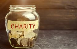 Glass jar with coins and the word Charity. The concept of accumulating money for donations. Saving. Social medical help from volun stock image