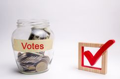 Glass jar with coins and the words Votes and a checkbox. Concept of voting for money. Bribing voters. Corruption in the electoral royalty free stock photo