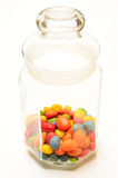 A glass jar with colored candies. On white background Stock Photography