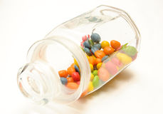 A glass jar with colored candies. On white background Royalty Free Stock Photo