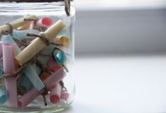 Glass jar with colored notes with blur and toning. Stock Photo