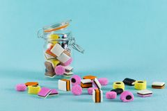 Glass jar with colorful candy liquorice allsorts. Bright minimalist background Stock Photography