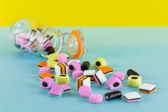 Glass jar with colorful candy liquorice allsorts bright minimalist background. Glass jar with colorful candy liquorice allsorts Royalty Free Stock Photos