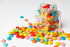 Glass jar with colorful candy scattered on the boards. festive background for your design. Candy scattered on the floor of the glass jar. Sweet Candy Stock Images