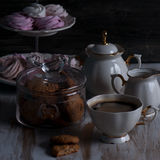 A Glass jar with cookies and a cup on a wooden table on dark background. Vintage Style Stock Photography