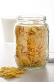 Glass jar of corn flakes with mug of milk Royalty Free Stock Image